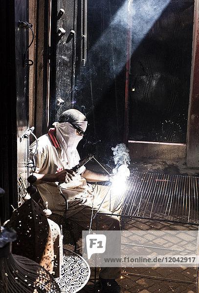 Worker in Blacksmiths Souk welding metal  Marrakech  Morocco  North Africa  Africa