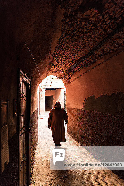 Local man dressed in traditional djellaba walking through archway in a street in the Kasbah  Marrakech  Morocco  North Africa  Africa