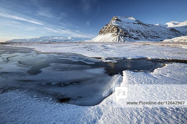 Snow covered landscape in winter with frozen pool  mountain and Vatnajokull Glacier  near Jokulsarlon Lagoon  South Iceland  Polar Regions