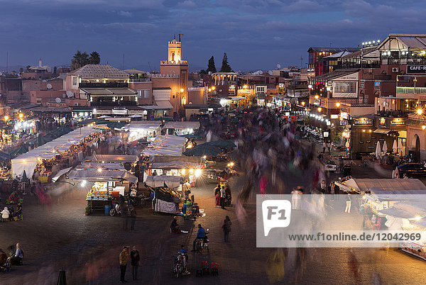 View over the Djemaa el Fna at dusk showing food stalls and crowds of people  Marrakech  Morocco  North Africa  Africa
