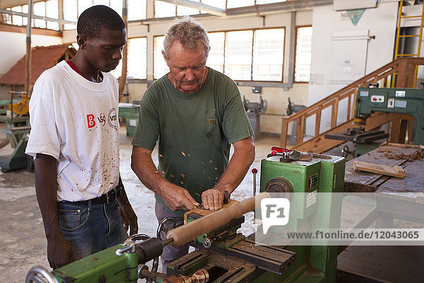 A VSO volunteer teaching how to use a lathe during a VSO woodwork vocational skills training workshop  Tanzania  East Africa  Africa