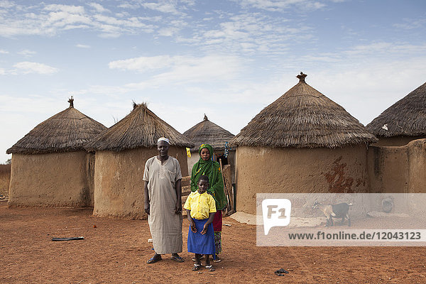 A young school girl with her parents outside their home in Tinguri  northern Ghana  West Africa  Africa