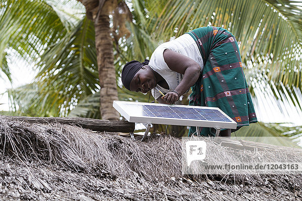 A woman  known as a Solar Mama  fixes a solar panel to the top of a traditional thatched mud hut  Tanzania  East Africa  Africa