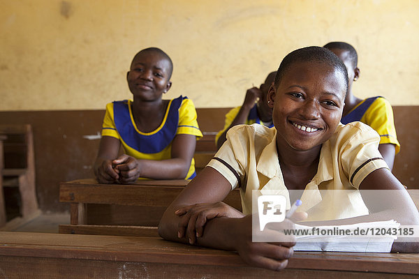 A portrait of a school girl smiling during a lesson in her classroom  Ghana  West Africa  Africa