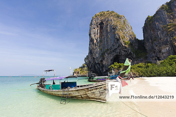 Traditional Longtail boats moored by Phra Nanag Beach with limestone cliffs in the background  Krabi  Thailand  Southeast Asia  Asia