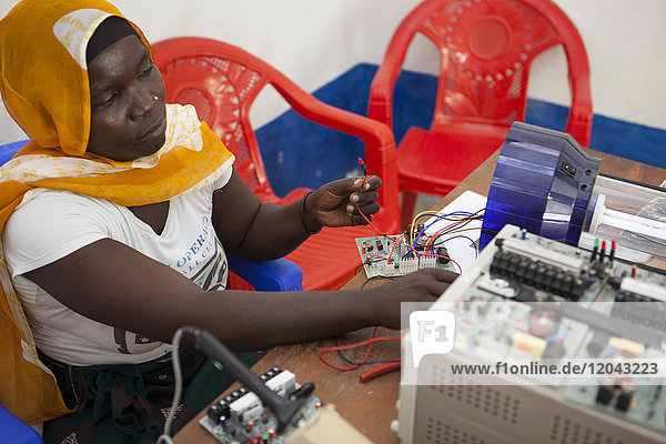A female solar engineer  known as a solar mama  works on the printed circuit board of a solar lamp  Tanzania  East Africa  Africa