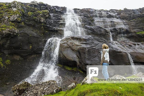 Woman looking at a waterfall in Estuyroy  Faroe islands  Denmark