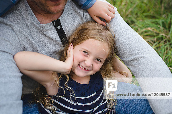 Vater sitzt mit Tochter auf grünem Grasfeld