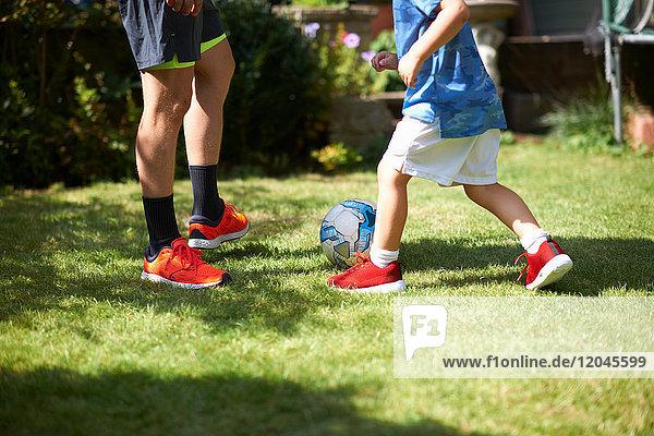 Vater und Sohn beim Fussballspielen im Garten  niedriger Abschnitt