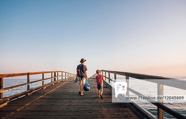 Rear view of father and son walking on pier  Goleta  California  United States  North America