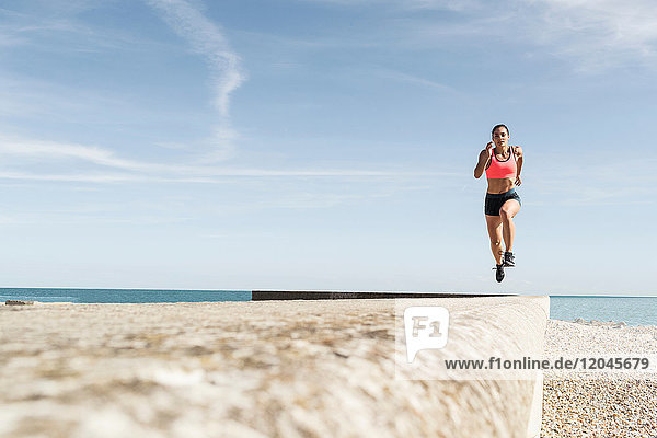 Young woman running along sea wall  mid air