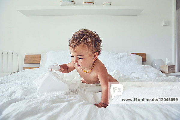 Toddler sitting on bed  holding unravelled toilet roll