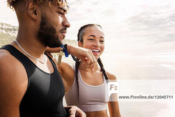Junge weibliche Läuferin ruht Arm auf der Schulter eines jungen Mannes am Strand