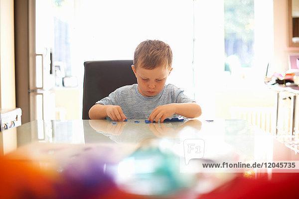 Junge  der am Tisch sitzt und mit Modelliermasse spielt
