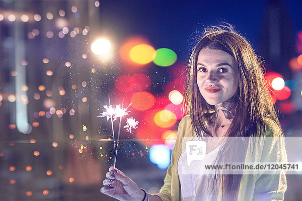 Portrait of young woman  outdoors at night  holding lip sparklers