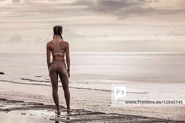 Rückansicht einer jungen Läuferin am Wasser mit Blick aufs Meer