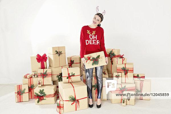 Junge Frau in rotem Pullover und Rentiergeweih bei gestapelten Weihnachtsgeschenken mit Weihnachtspäckchen