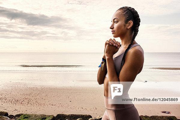 Junge Läuferin bereitet sich am Strand mit vereinten Händen auf den Lauf vor