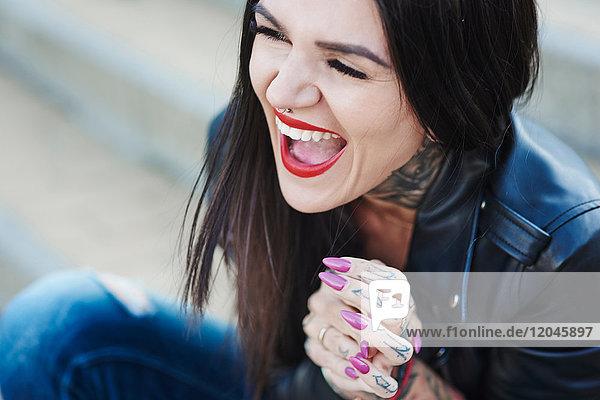 Porträt einer lachenden jungen Frau  Tätowierungen an Hals und Hand