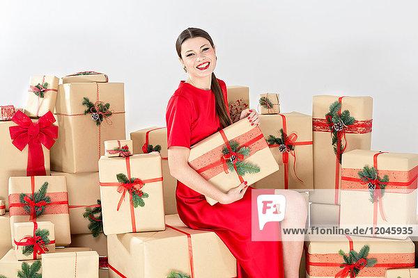 Porträt einer jungen Frau in rotem Kleid  die auf gestapelten Weihnachtsgeschenken sitzt und ein Weihnachtspäckchen hält