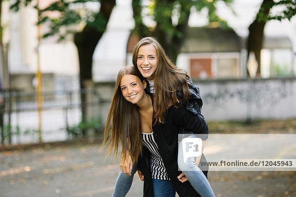 Porträt einer jungen Frau  die ihrem besten Freund im Park ein Huckepack gibt