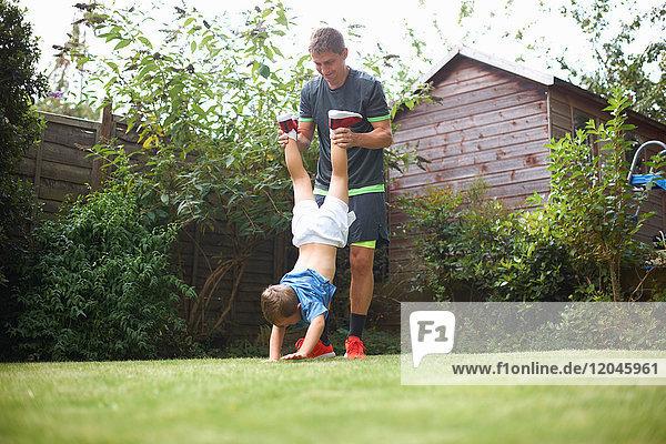 Vater und Sohn im Garten  die Hände des Sohnes im Gras  der Vater hebt die Beine