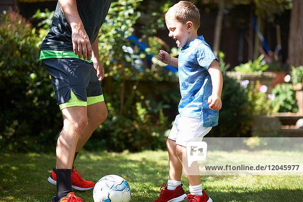 Vater und Sohn spielen im Garten Fussball