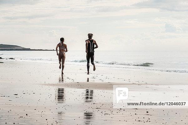Rückansicht junger männlicher und weiblicher Läufer  die barfuss am Strand entlang laufen