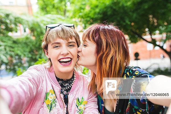Zwei junge Frauen im Retro-Stil beim Selfie im Park