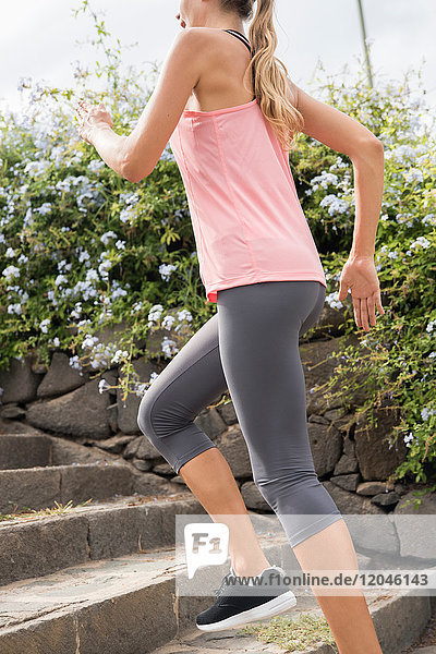 Side view of woman jogging up steps