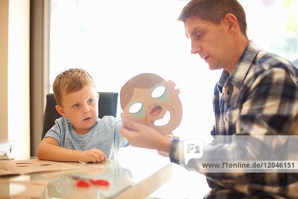 Vater und Sohn  am Tisch sitzend  Maske anfertigen