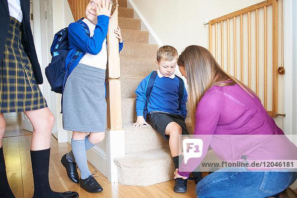 Frau zieht auf der Treppe den Schulschuh des Sohnes an