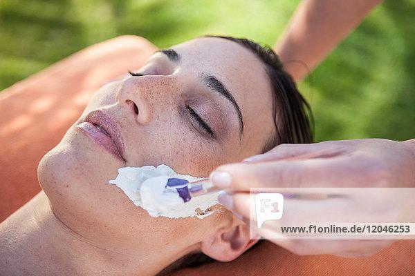 Frau in Wellness-Umgebung  Gesichtsmaske wird auf ihr Gesicht aufgetragen