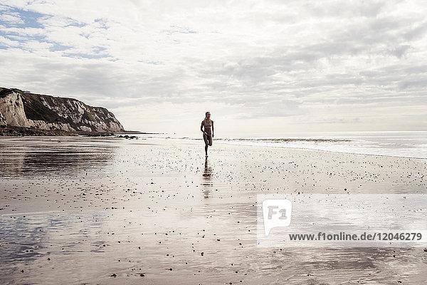 Junge Frau rennt am Strand entlang