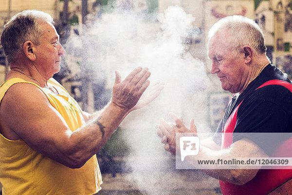 Zwei ältere männliche Kraftdreikämpfer kreiden ihre Hände in der Turnhalle