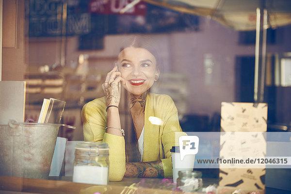 Junge Frau sitzt in Café  benutzt Smartphone  Tätowierungen auf der Hand  Blick durch Caféfenster