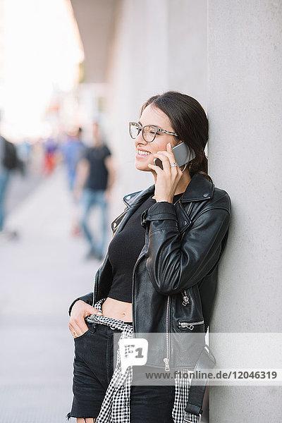 An die Wand gelehnte Frau mit Smartphone