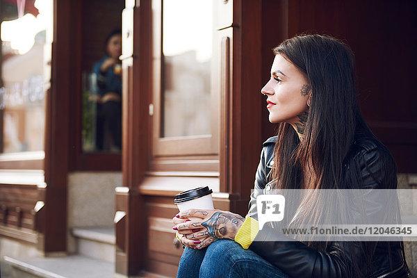 Junge Frau sitzt im Freien  hält Kaffeetasse  Tätowierungen auf Händen