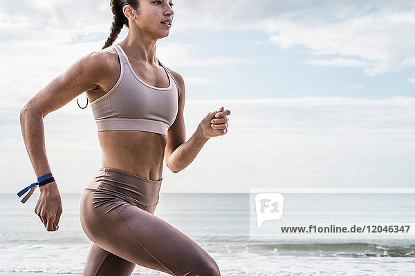 Young woman running along beach  close-up  mid section