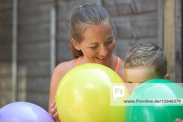 Mutter und Sohn im Garten  Ballons haltend