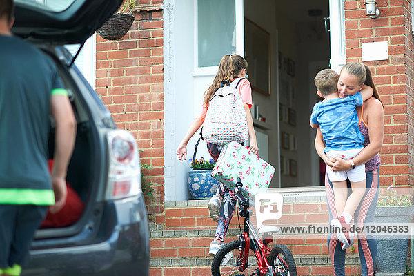 Familie packt Auto nach dem Urlaub aus