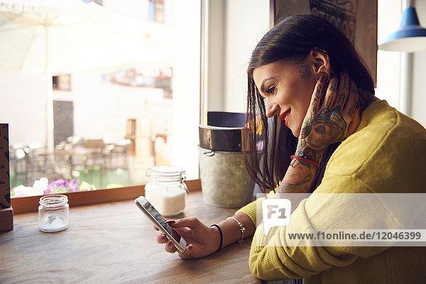 Junge Frau sitzt im Café  benutzt Smartphone  Tätowierungen auf Arm und Hand