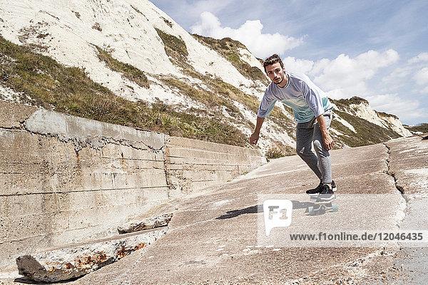 Junge männliche Skateboarder skateboarden an Klippe Seewand