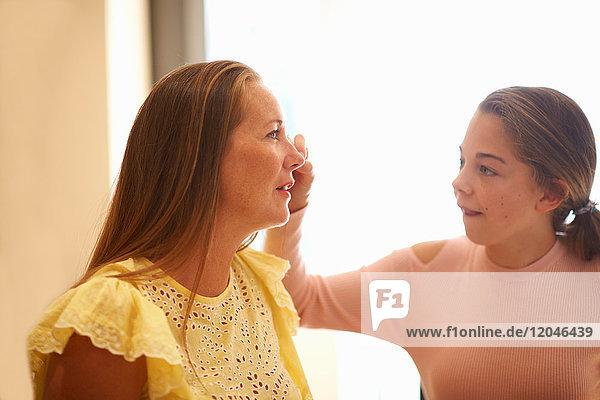 Junges Mädchen malt auf dem Gesicht der Mutter  mit Gesichtsfarbe