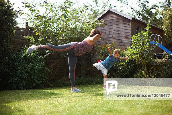 Mutter und Sohn üben im Garten  stehend in Yogastellung