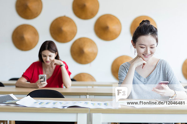 Students using mobile phone while waiting in class