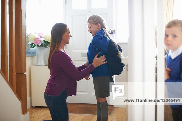 Frau kontrolliert Schuluniform der Tochter auf dem Flur