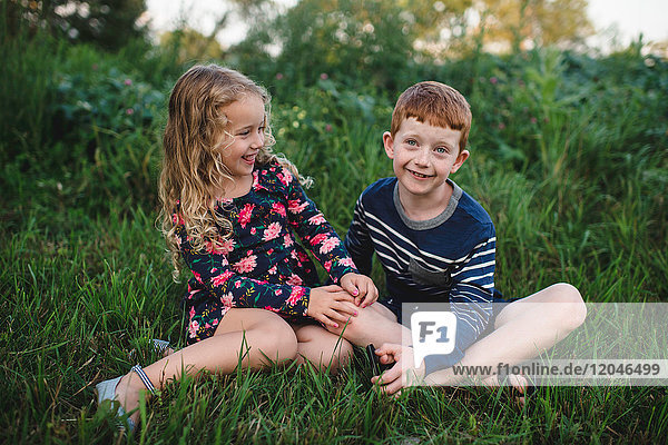 Girl and brother sitting in field