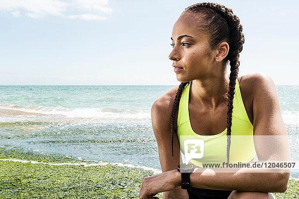 Junge Frau in Sportkleidung  am Meer kauernd