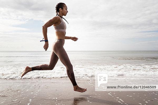 Seitenansicht einer jungen Läuferin  die am Strand barfuss am Wasser entlang läuft